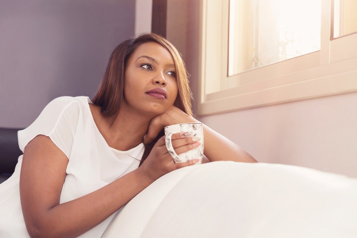 Self-care is more important than ever during a pandemic, whether we're in isolation or have to work outside. Photo: A woman looks out a window while leaning on the back of a futon couch. She's holding a cup of tea.