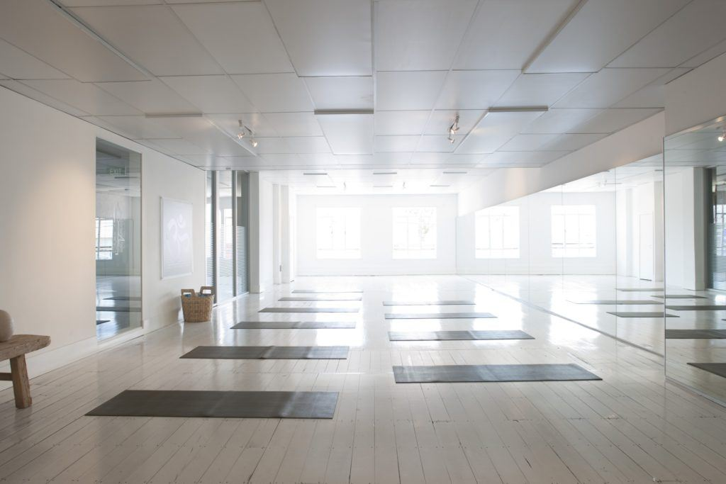 Photo: An empty, sunlit yoga studio, with yoga mats ready for students.