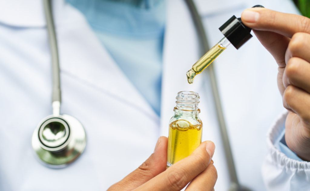 Matt and Kit answered CBD health questions on the Ministry of Hemp podcast, including questions about talking to doctors about CBD. Photo: A doctor wearing a lab coat and stethoscope, and holding a CBD bottle and dropper top.