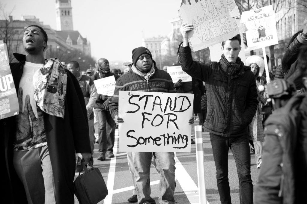 """In a black and white photo at a Black Lives Matter protest, a black marcher holds a handwritten sign reading """"Stand For Something."""""""