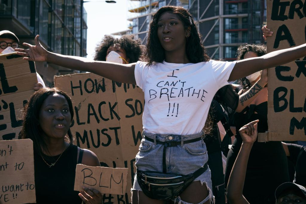 """Photo: A Black woman in a handmade """"I Can't Breathe"""" shirt holds her arms open in front of a crowd at a protest."""