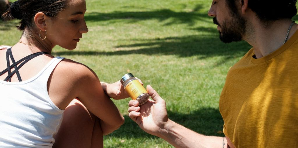 Sitting in a park, a man and woman exchange a bottle of FOCL Day, a supplement including CBD that promotes natural focus and energy.