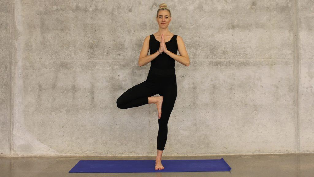"""A woman does the yoga """"tree pose"""" while standing on a yoga mat, against a bare cement wall background."""