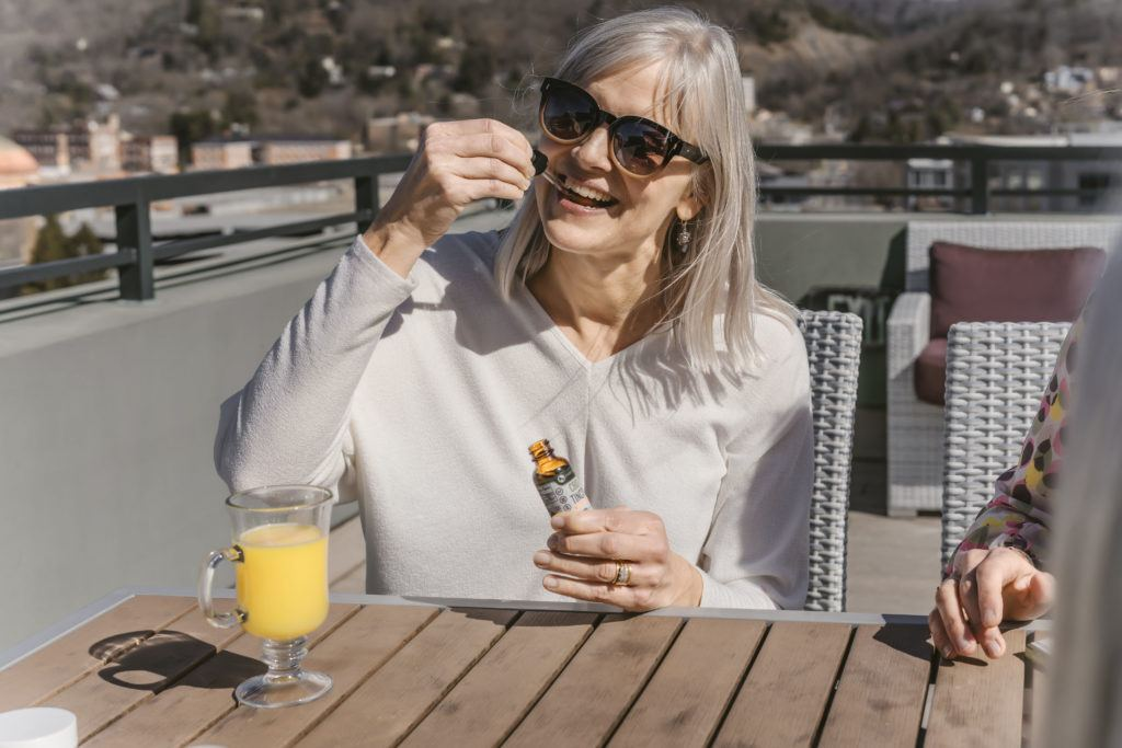 Photo: An older white woman with gray hair smiles as she takes Every Day Optimal CBD oil while sitting at an outdoor cafe.