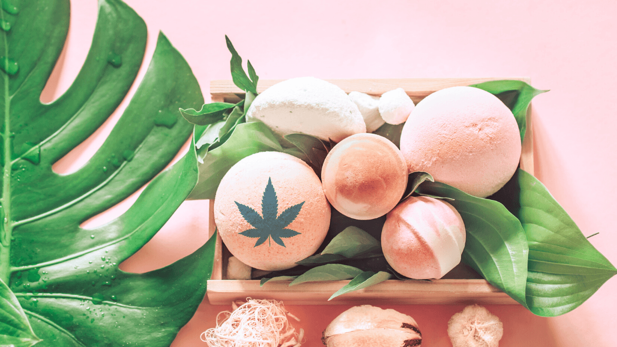 We reviewed the best CBD bath bombs and soaks. A photo of pink bath bombs artfully arranged in a box with sea shells and big green leaves. One bath bomb is digitally imprinted with a hemp leaf.