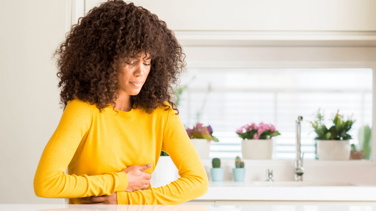 Can CBD help ease nausea? Photo: A black woman with natural hair, wearing a yellow sweater and standing in a kitchen, holds her stomach as if nauseous or in stomach pain.