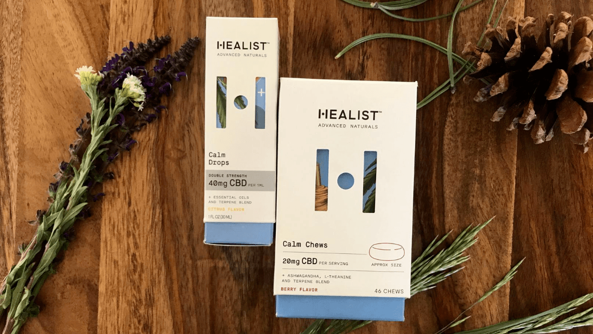 The box and CBD product label for two Healist Naturals produts, arranged with a pine cone and herbs.