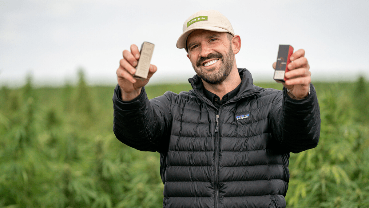 On the Ministry of Hemp Podcast, we learned about how Brandon Stump used CBD for addiction recovery, leading him to found his own company, Pachamama. Photo: Brandon Stump, founder of Pachamama CBD, holds two boxes of his products in a hemp field.