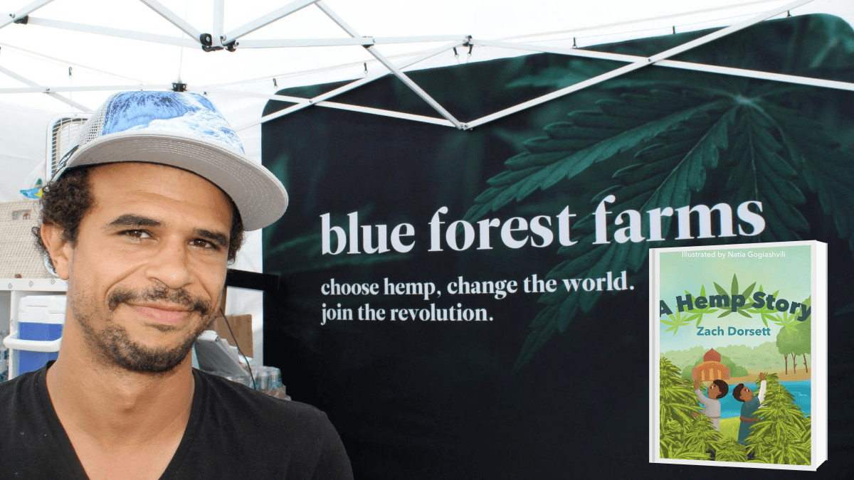 "Photo: A photo of Zach Dorsett under a Blue Forest Farms awning. The motto reads ""choose hemp. change the world. join the revolution."" Also pictured is his hemp children's book, ""A Hemp Story."""