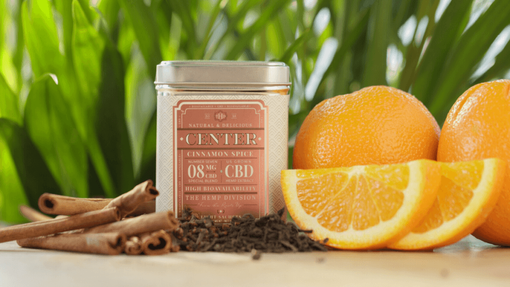 A tin of Cinnamon Spice CBD tea from Harney & Son's The Hemp Division, posed with oranges and cinnamon sticks.
