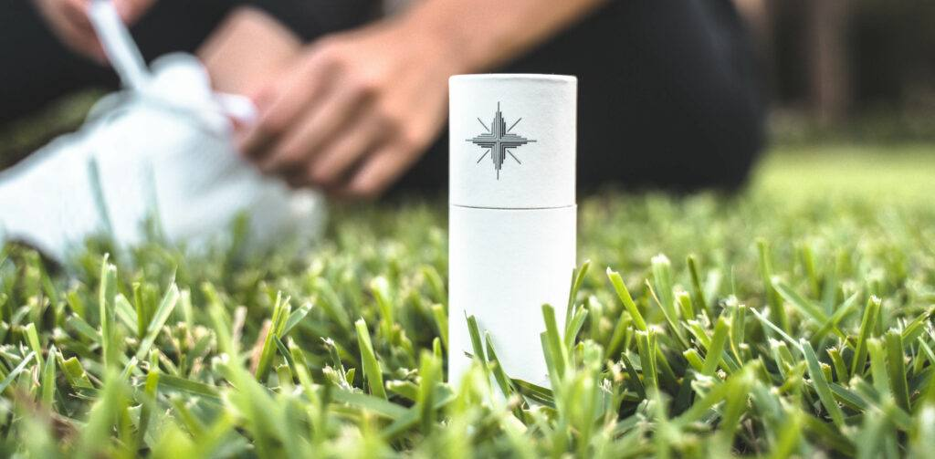 A bottle of Canvas 1839 CBD oil sits on a fake grass surface while, in the background, someone ties their athletic shoes.