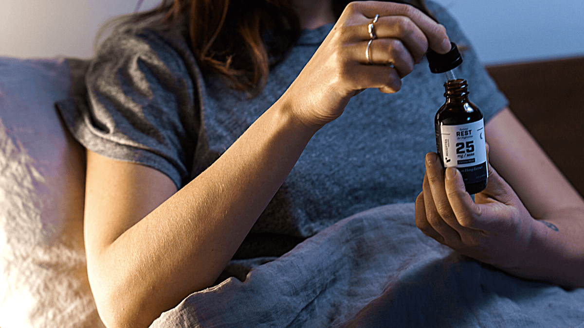 A person sitting up in bed takes Receptra Naturals Serious Rest tincture from a dropper bottle.