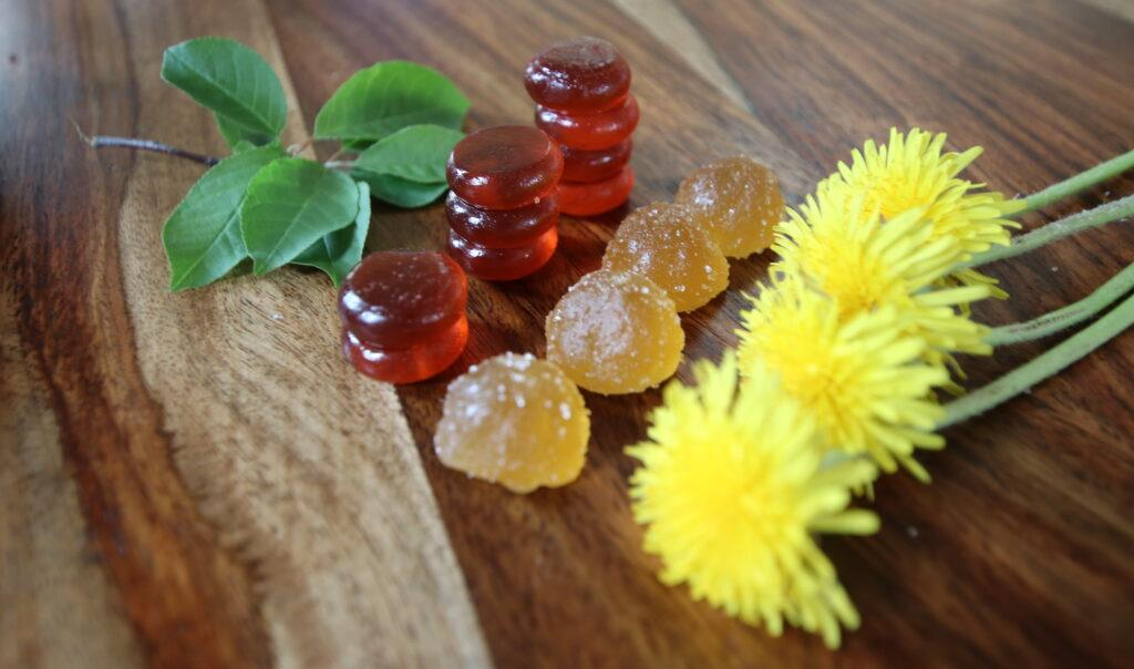 Different styles of CBD gummies or chews decoratively posed with mint leaves and dandelion flower on a richly grained, smooth wooden surface.