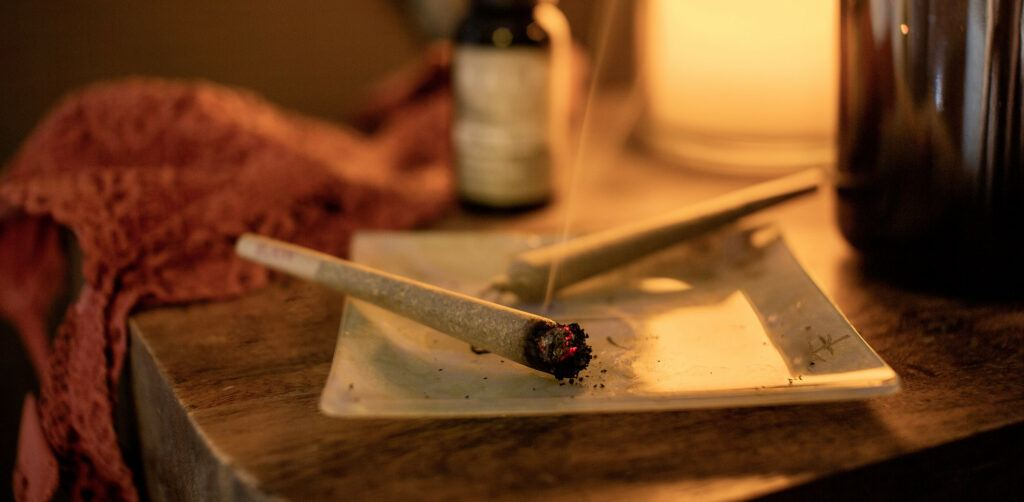 A pre-rolled hemp flower joint smokes in a white ashtray, with another unlit nearby. The ashtray sits on an end table with CBD oil, a tea cup and some fabric in the background.