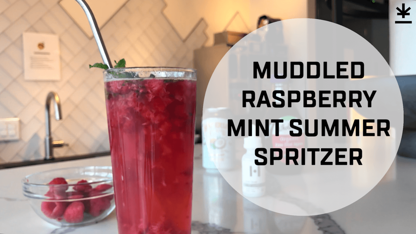 "A glass of raspberry CBD spritzer with a metal straw in it, garnished with a mint leaf. Text reads ""Muddled Raspberry Mint Summer Spritzer."""
