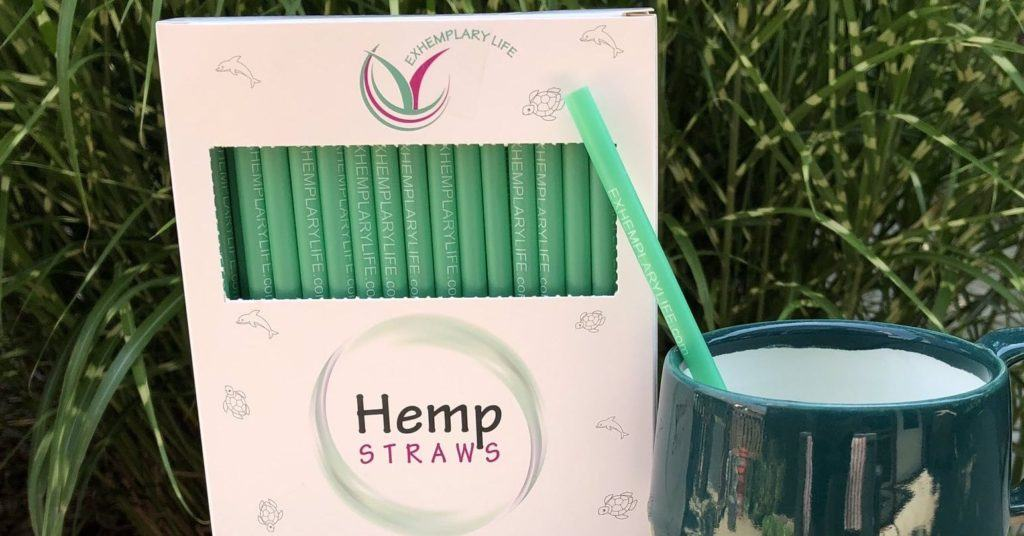 A box of ExHemplary Life hemp plastic straws posed against a grassy background, with a mug holding a straw nearby.
