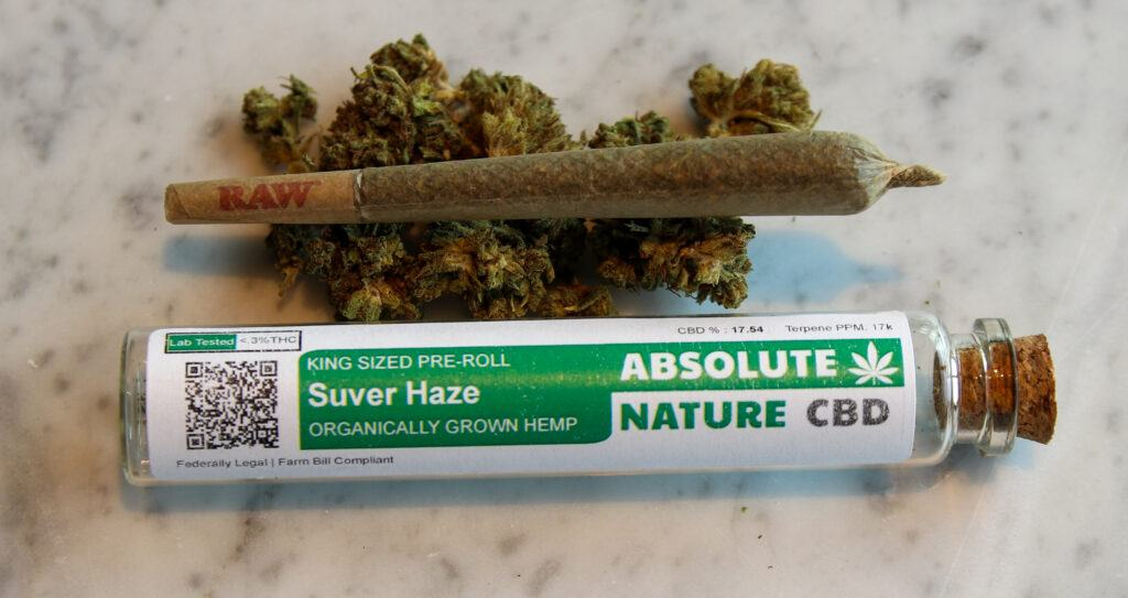 """A CBD pre-roll posed with hemp flower, along with an Absolute Nature pre-roll """"doob tube"""" made from sustainable glass and cork, posed on a marble countertop."""