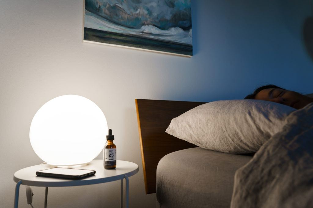 A person sleeps soundly in their bed, with a bottle of Receptra Naturals Serious Rest Tincture on the bedside table near a globe-shaped lamp and a smartphone.