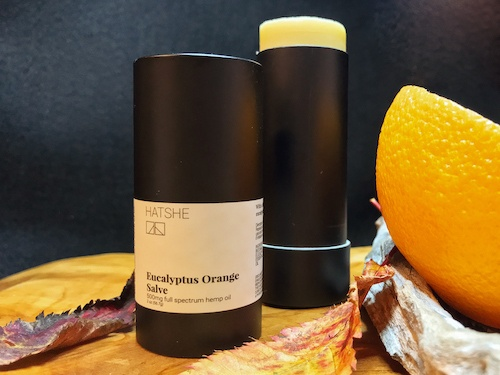 Hatshe Eucalyptus Orange Salve resting next to an orange slice on a natural wooden base.