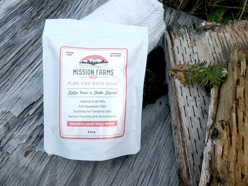 Mission Farms Bath Soak arranged outdoors on a log, with a white rolled up towel.