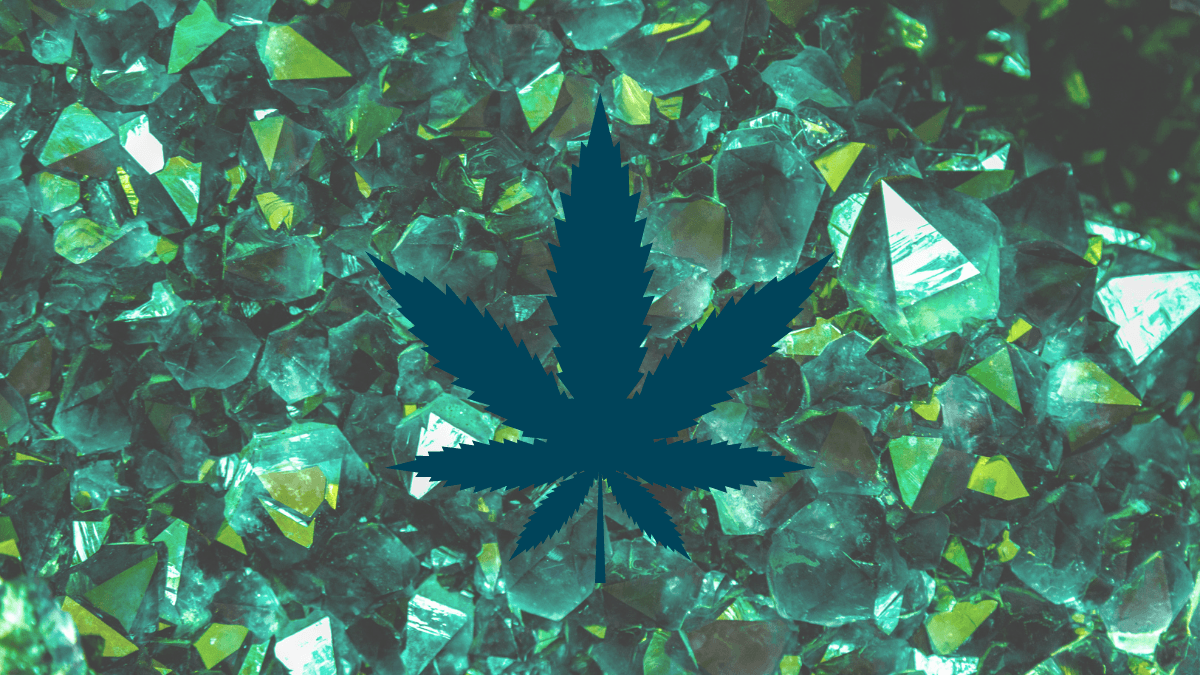 CBD cocrystals could improve bioavailability and change how we take CBD. Photo: Green crystals such as emeralds, clustered together naturally. A dark green hemp leaf is superimposed on the image.