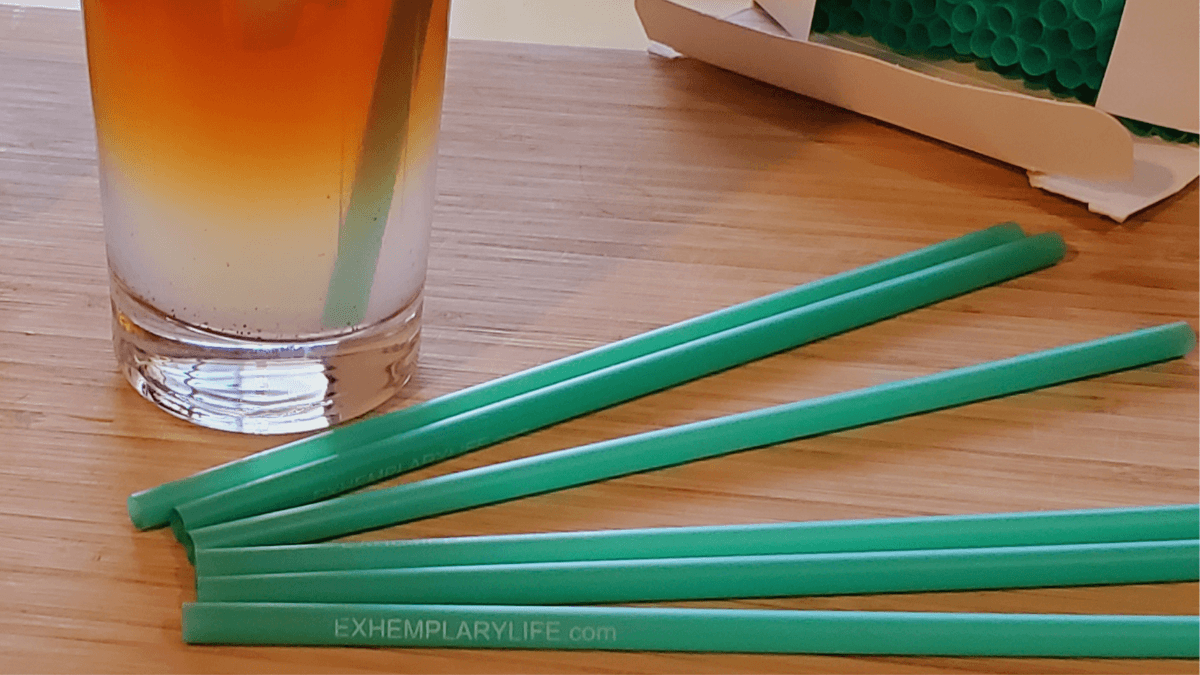 Hemp straws on a bamboo cutting board, next to a glass of Arnold Palmer (lemonade and iced tea) containing a hemp straw and a box of straws.