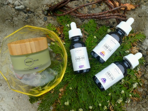 Royal & Pure products arranged outdoors on a green organic background, including a topical CBD balm and CBD tinctures.