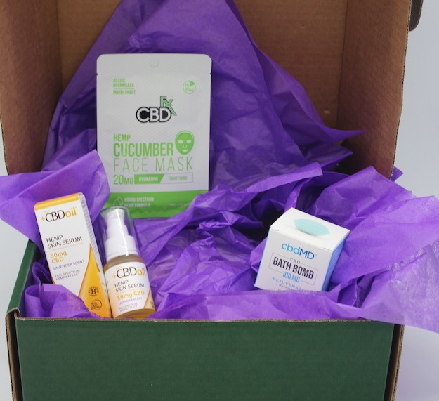 Green Wellness Life skin soother gift box CBD skin care products with purple tissue paper for decoration.