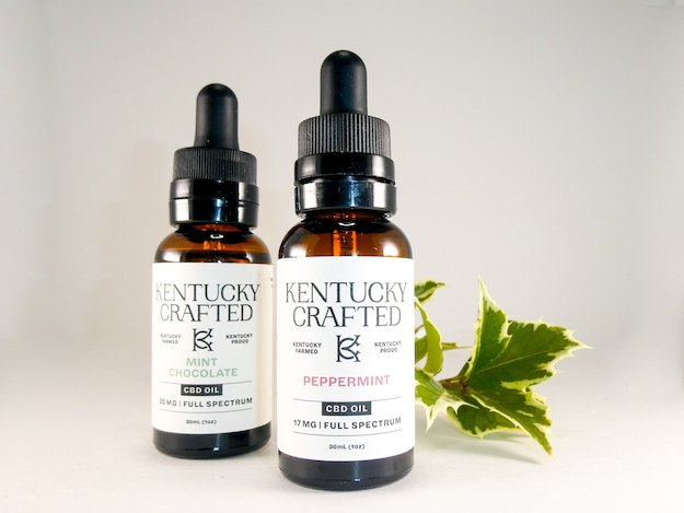 Two Kentucky Crafted CBD oil tinctures with a decorative sprig of ivy.