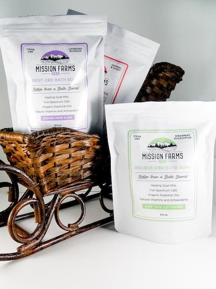 Mission Farms CBD Bath Soak pouches in a wicker basket shape like a sled.