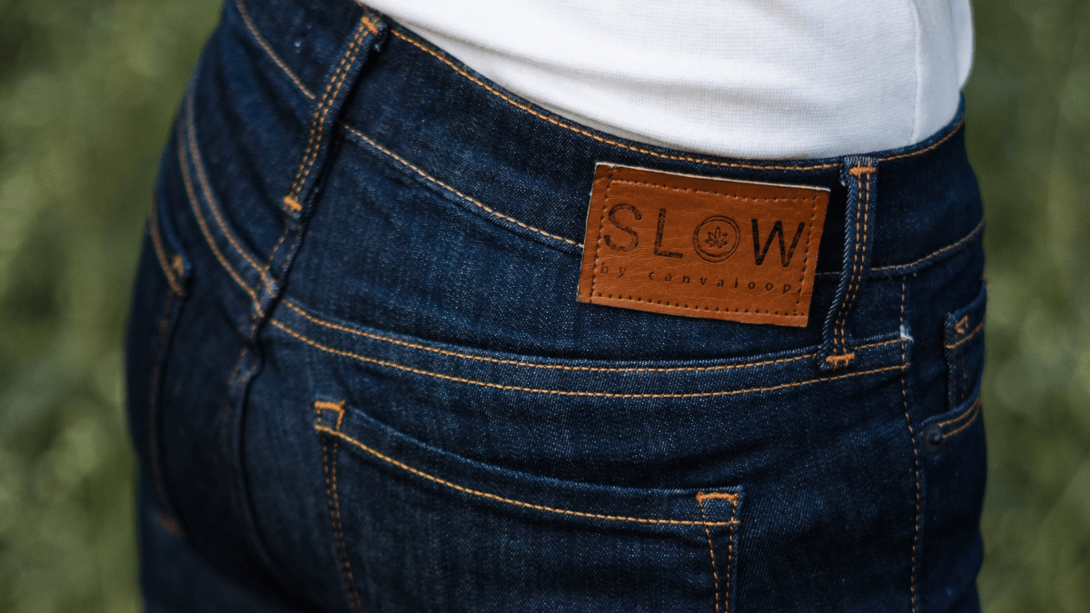 A closeup of a person seen from behind, wearing a white-tshirt and Slow Hemp blue jeans. Just the lower part of the shirt and the back part of the jeans with the tag is visible.