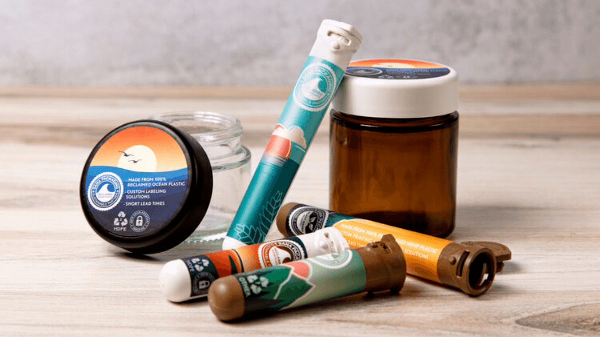 "A collection of hemp plastic packagiing and packaging made from ocean plastic, designed for cannabis and hemp products, including jars and ""doob tubes."""