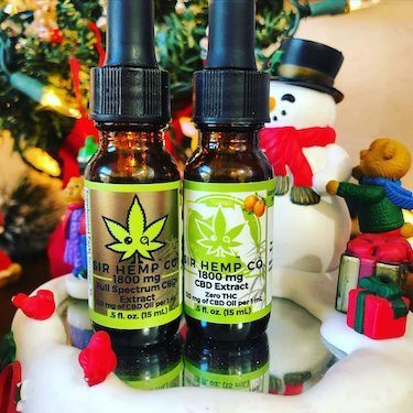Two bottles of Sir Hemp Co CBD oil, surrounde dby a snowman, fake snow and other Christmas props.