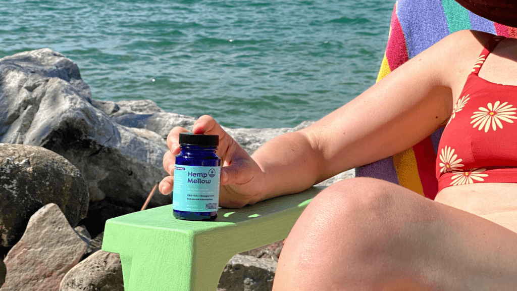 A seated woman at the beach in a sun hat, face just out of frame, holds a bottle of Hemp Mellow.